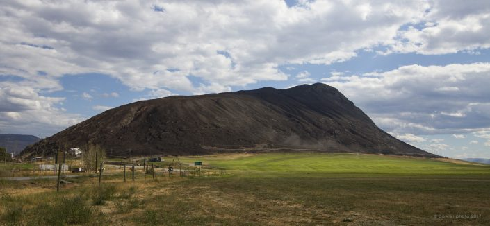 A large burned hill stands on a green irrigated landscape.