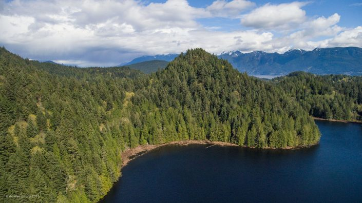 A conical hill covered in temperate rainforest near deep blue Grafton Lake on Bowen Island, BC