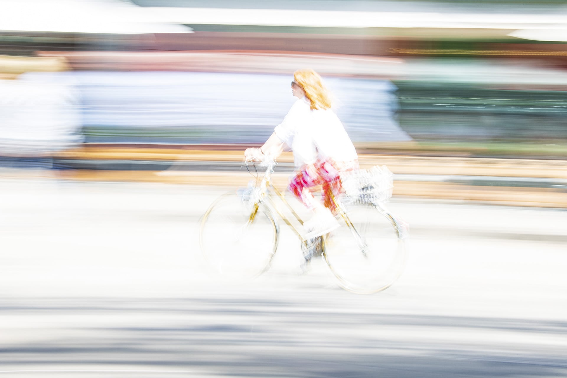 a bright, blurred image of a woman riding a bike with a crisp profile against stripes of colour.