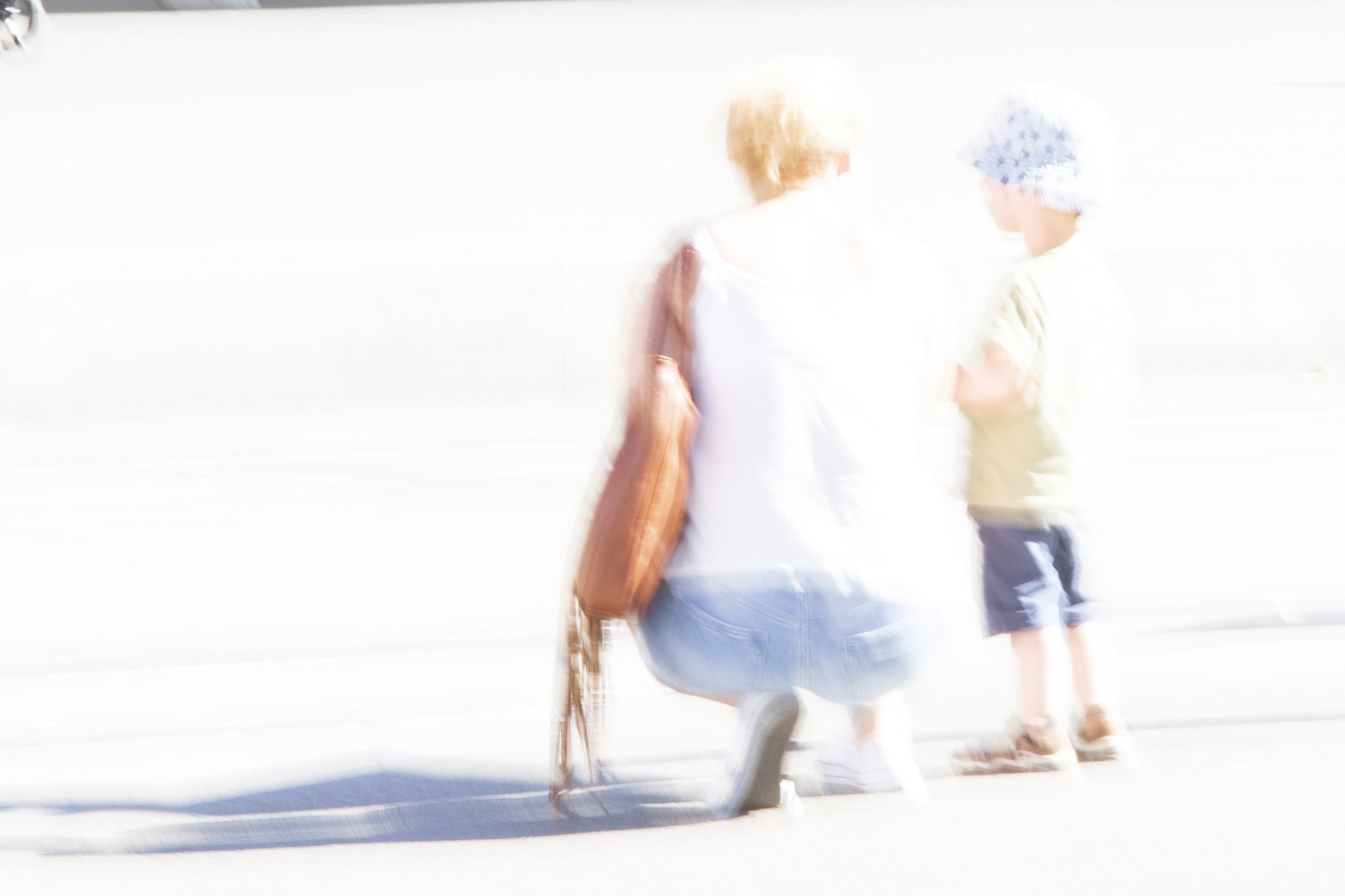 a bright white images with bright coloured ghostly image of crouching grandmother with young child beside her from behind.