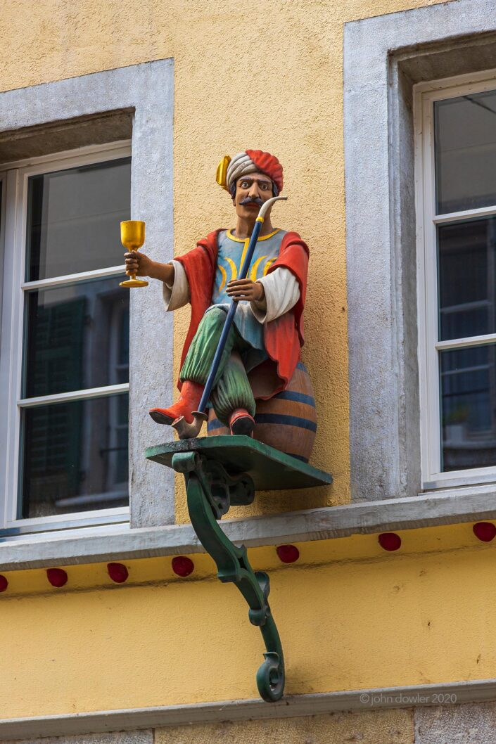 A carved wooden man in Turkish attire offering a meter-long pipe and a golden goblet from a platform on a wall in Solothurn, Switzerland.
