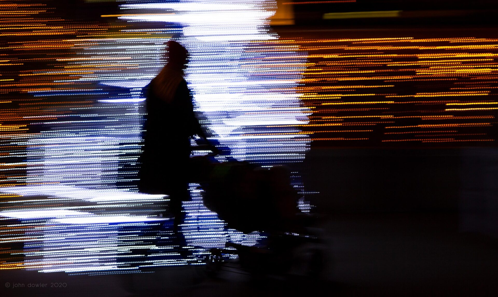 a black silhooet of a mother pushing a stroller against colourful streaks of light composed of discrete square dots; a mosaic of light