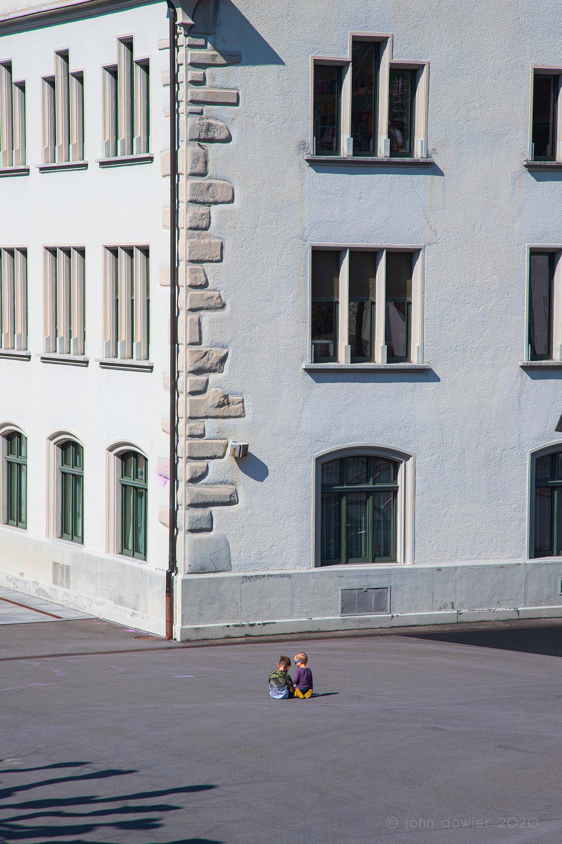 in a broad courtyard beneath a tall white building two tiny boys face away from the camera looking at something in their hands.