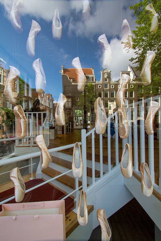 ballet slippers reflect in a window appear to float in the reflection of the city of Amsterdam