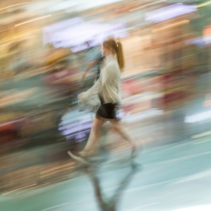 A blurry woman walks down a steep incline past streaks of colour